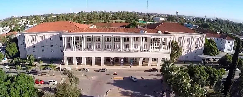 El Pabellón Argentina de Ciudad Universitaria en un día soleado visto desde el frente con una cámara en un drone