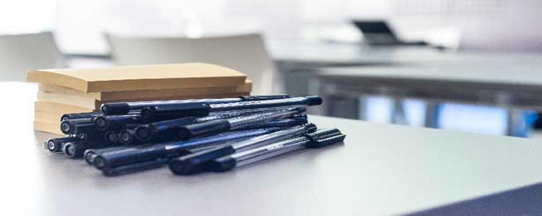 lapiceras y cuadernos sobre escritorio
